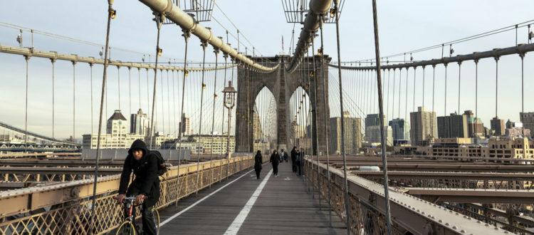 A biker goes accross the bridge.